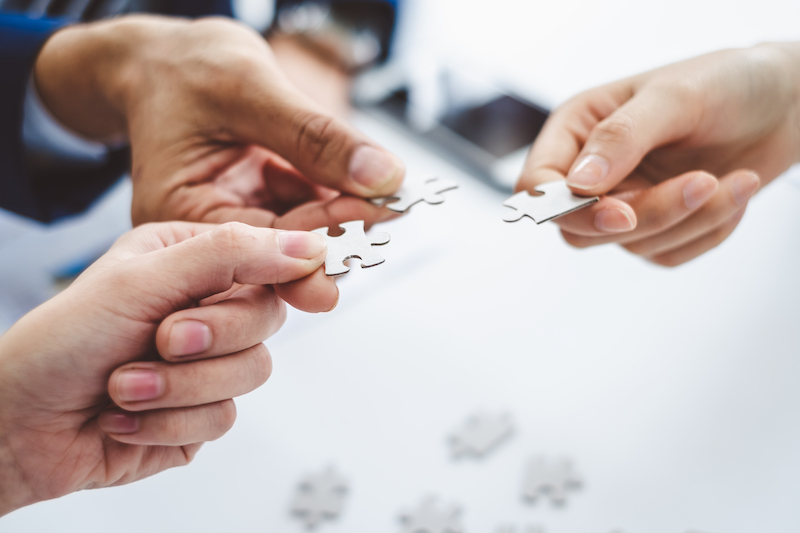 Hand business man holding jigsaw puzzle for connection teamwork together concept